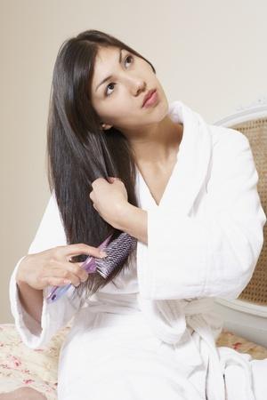 Woman in robe brushing hair