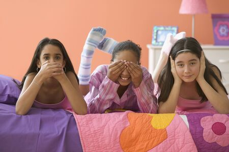Three girls posing with hands over mouth, eyes and ears