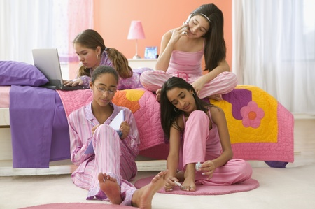 Four girls sitting in bedroom with computer, journal, cell phone and fingernail polish
