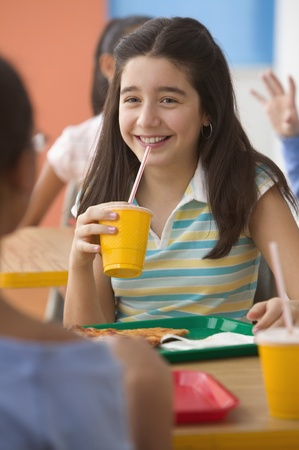 all under 18: Four girls eating lunch in cafeteria
