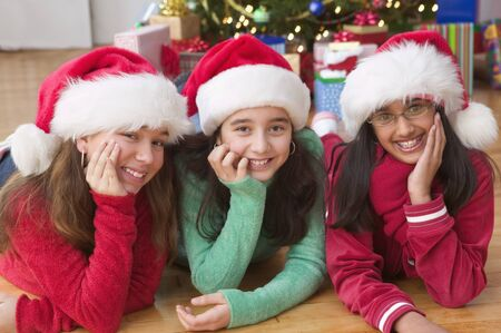 Portrait of three girls with Santa hats in front of Christmas tree 스톡 콘텐츠