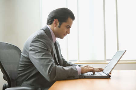 above 18: Profile of businessman sitting at desk working on laptop computer