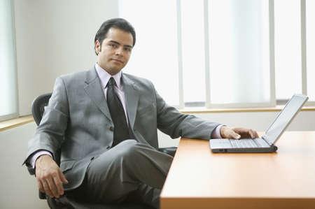 above 18: Portrait of businessman sitting at desk with laptop  computer LANG_EVOIMAGES