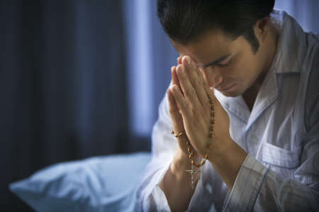 communication: Man in pajamas holding rosary and praying
