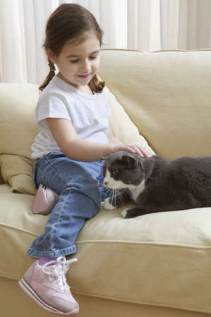 all under 18: Young girl petting cat on couch