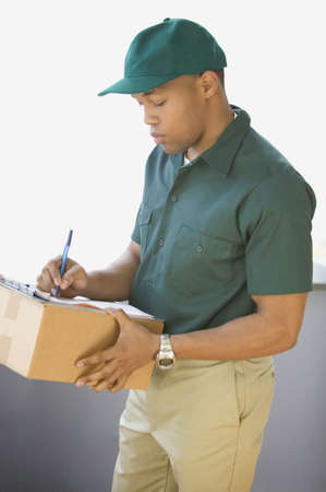 man side view: Profile of delivery man writing notes and holding box LANG_EVOIMAGES