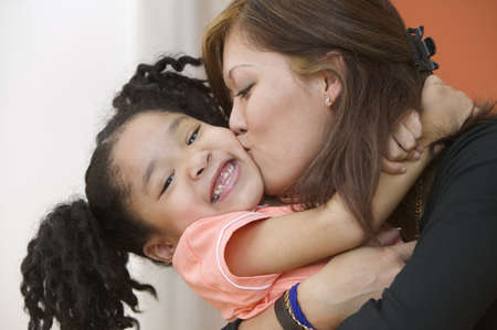 some under 18: Portrait of mother hugging and kissing young daughter