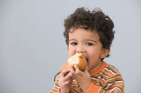 Portrait of young boy eating pear Stock Photo - 16072365