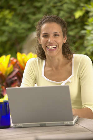 mid afternoon: Portrait of woman sitting at table with laptop