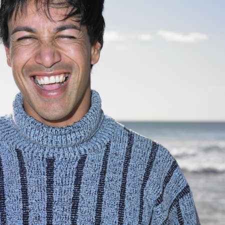 above 30: Young man smiling at beach