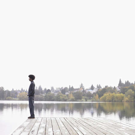 above 25: Man on dock by lake LANG_EVOIMAGES