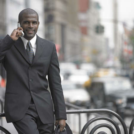 phone: Businessman walking while talking on cell phone LANG_EVOIMAGES