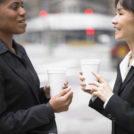 above 30: Businesswomen talking while drinking coffee LANG_EVOIMAGES