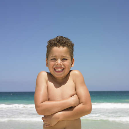 behaving: Smiling boy standing on beach