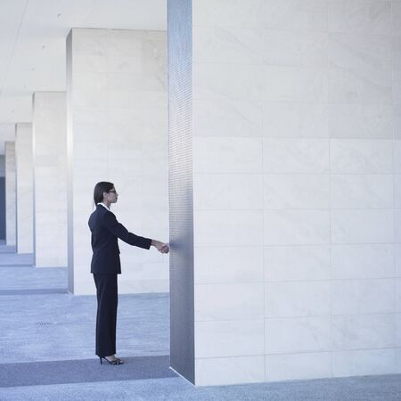 above 25: Businesswoman shaking hand behind wall