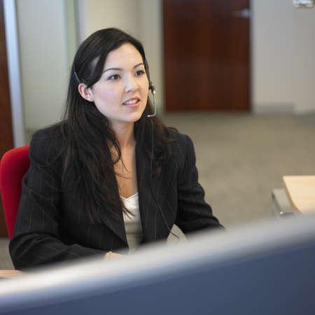 earpiece: Woman sitting in office wearing earpiece LANG_EVOIMAGES