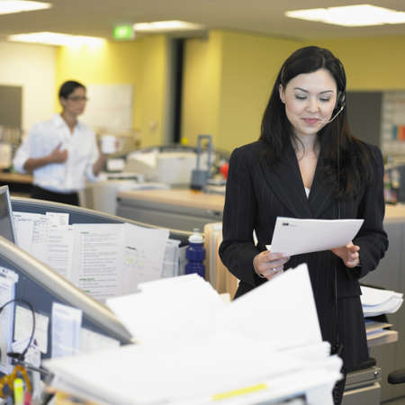 above 21: Businesswoman reading paper in office