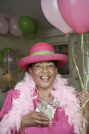 Portrait of senior adult woman in feather boa and hat with balloons Stock Photo - 16072569