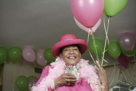Portrait of senior adult woman in feather boa and hat with balloons Stock Photo - 16072570