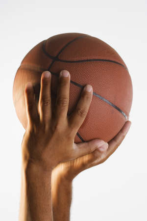 above 30: Close up of hand holding basketball in air