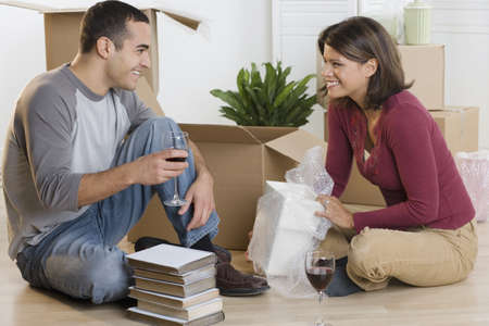 above 25: Couple unpacking boxes and drinking wine LANG_EVOIMAGES