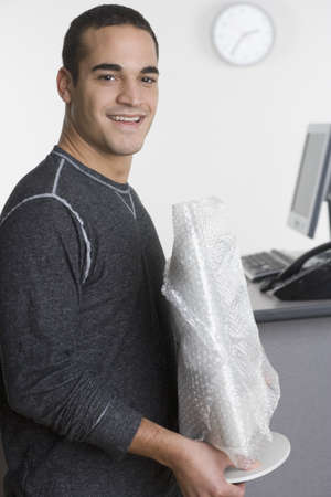 above 25: Portrait of man holding object in office LANG_EVOIMAGES