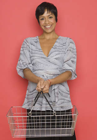 grocery basket: Portrait of woman holding grocery basket