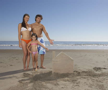 some under 18: Portrait of family on beach showing sandcastle
