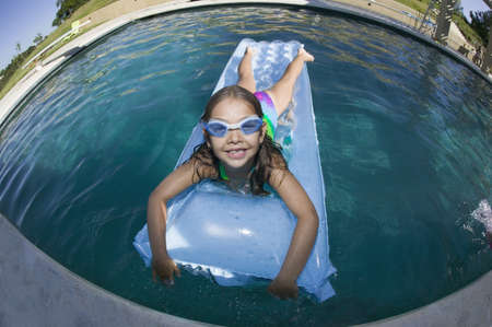 all under 18: Girl in swimming pool laying on air mattress