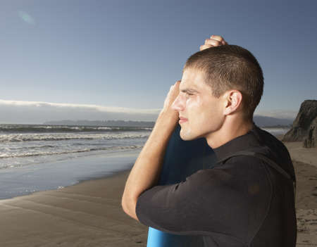 wet suit: Profile of man in wet suit at beach with surf board LANG_EVOIMAGES