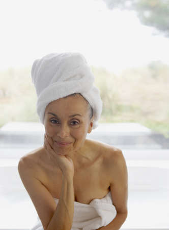 woman bath: Portrait of senior woman wrapped in towel with towel on head