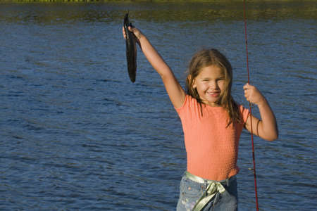 fishing pole: Portrait of girl holding up fish and fishing pole