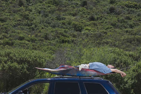 above 25: Man laying in kayak on top of car LANG_EVOIMAGES