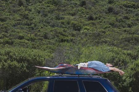 resourceful: Man laying in kayak on top of car LANG_EVOIMAGES
