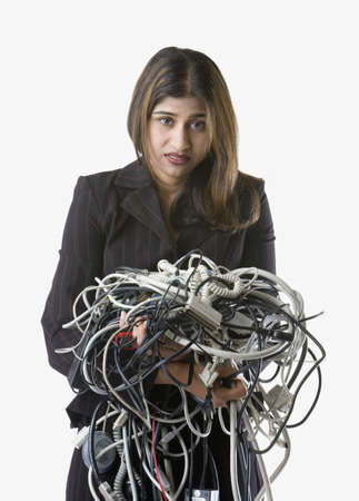 discouraging: Businesswoman holding tangled computer cords LANG_EVOIMAGES