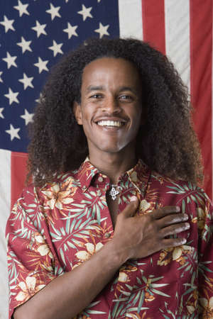 ethiopian ethnicity: Portrait of man with hand over heart standing in front of American flag LANG_EVOIMAGES