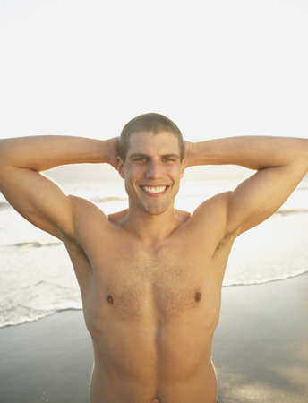 above 25: Portrait of man without shirt smiling with hands behind head