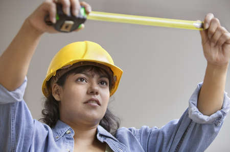 above 30: Woman construction worker with measuring tape and hard hat