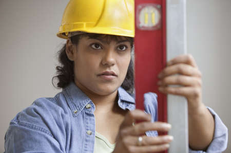 construction level: Woman construction worker in hard hat reading level measurements