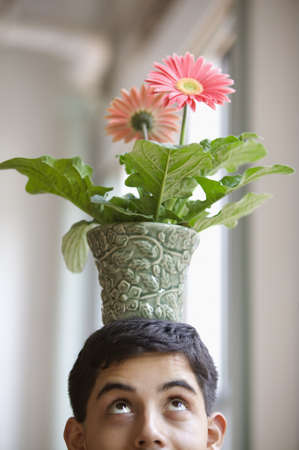 behaving: Close up of young adult man balancing potted flower on head LANG_EVOIMAGES