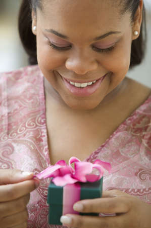 above 25: Close up of African American woman opening gift