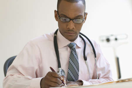 Male doctor writing notes LANG_EVOIMAGES