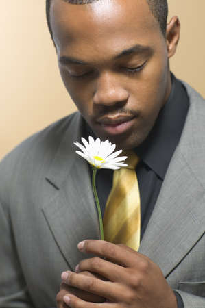 holding close: Man in suit holding daisy