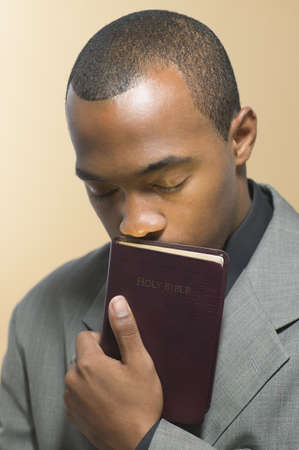 Man with eyes closed kissing Bible Stock Photo