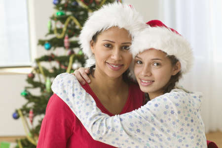 some under 18: Portrait of mother and daughter with Christmas tree behind them
