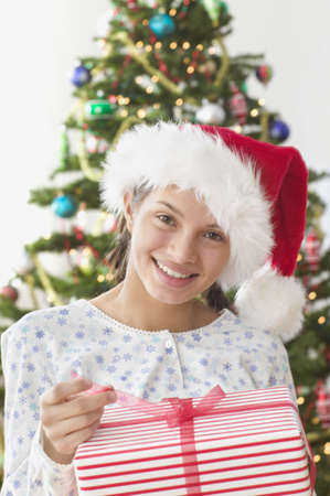 all under 18: Girl pulling the ribbon off Christmas present LANG_EVOIMAGES