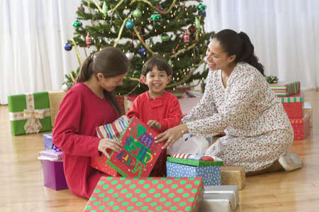 tradition: Family opening gifts on Christmas day in front of tree