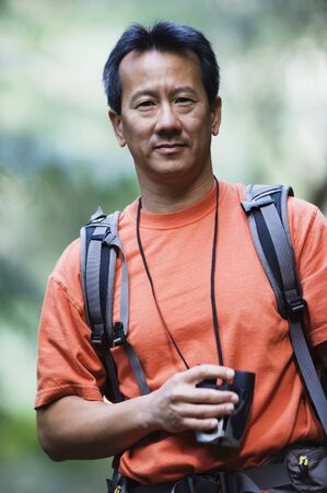 above 30: Portrait of man holding binoculars while hiking