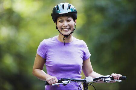 Portrait of woman with bike wearing bike helmet