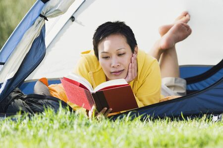 above 30: Woman laying in tent reading book